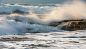 Rocky seashore with wavy ocean and wind waves crashing on the ro Stock Photography