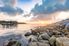 Rocky seashore with Wooden plank pier in beautiful sunrise Royalty Free Stock Photo
