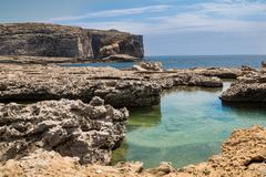 Sea shore with a mountain, Gozo, Malta. Rocky seaside. Rocks creating a small lake. Horizon of the mediterranean sea. Mountain in the background. Blue sky with Royalty Free Stock Images