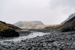 Free Rocky Shallow Mountain River In Iceland, Flows Against The Backdrop Of Mountains. Stock Photo - 185466920