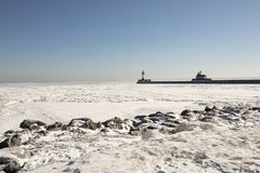 Rocky shore along frozen Lake Superior with pier and lighthouses Royalty Free Stock Photography