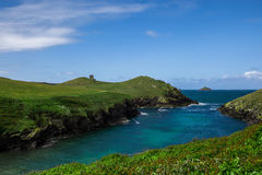 Rocky shore. Rocky atlantic shore of United Kingdom with green pastures blue sky and ocean Stock Images