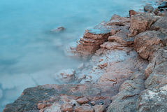 Rocky shore in azure water Stock Image