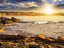 Rocky shore and a beach of Black sea at sunset. SOZOPOL, BULGARIA - SEPTEMBER 11, 2013: rocky shore and sandy city beach in mellow season. Beautiful and warm royalty free stock images