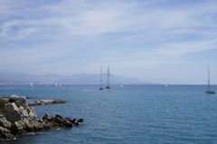 Rocky shore with boats in Antibes, French Riviera Royalty Free Stock Photo