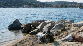 Rocky shore. Chair on the rocky shore in the Porto Koufo bay, Greece stock images