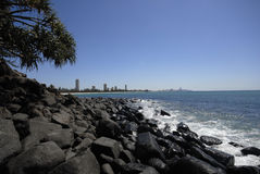 Rocky shore and city skyline Stock Photo