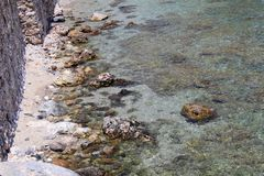 Rocky shore and crystal clear water near the fortress wall Alanya, Turkey Stock Photo