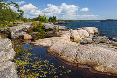 Rocky shore in Georgian Bay. Rock formations at rocky lake shore of Georgian Bay near Parry Sound, Ontario Canada Royalty Free Stock Images