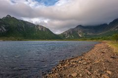 Rocky shore with green mountain peaks royalty free stock images