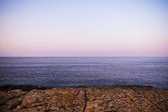 Rocky Shore, il Mediterraneo e l'orizzonte durante il tramonto Fotografie Stock