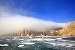 Rocky shore of lake Baikal in the fog in winter. Rocky headland on the Western coast of lake Baikal sticks in ice-covered body of water, Fog hampers visibility Stock Photography