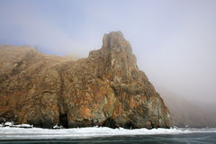 Rocky shore of lake Baikal in the fog in winter. Rocky headland on the Western coast of lake Baikal sticks in ice-covered body of water, Fog hampers visibility Royalty Free Stock Photos