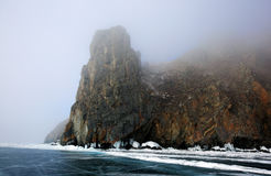 Rocky shore of lake Baikal in the fog in winter. Rocky headland on the Western coast of lake Baikal sticks in ice-covered body of water, Fog hampers visibility Royalty Free Stock Photo