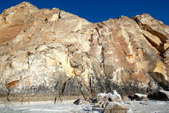 Rocky shore of lake Baikal in winter. Rocky headland on the Western coast of lake Baikal sticks in the ice-covered pond Royalty Free Stock Photos