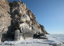 Rocky shore of lake Baikal in winter. Rocky headland on the Western coast of lake Baikal sticks in the ice-covered pond Royalty Free Stock Photo
