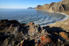 Rocky shore of lake Baikal in winter. Rocky headland on the Western coast of lake Baikal sticks in ice-covered water body, forming a cozy Bay with a pebble beach Royalty Free Stock Photography