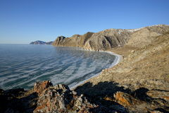 Rocky shore of lake Baikal in winter. Rocky headland on the Western coast of lake Baikal sticks in ice-covered water body, forming a cozy Bay with a pebble beach Stock Images