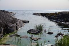 Rocky shore of lake Ladoga. Out of the water are the rocks and plants. There are many Islands on the horizon. Clear sunny day. royalty free stock photo