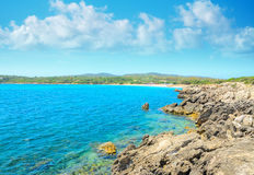 Rocky shore with Lazzaretto beach in the background Royalty Free Stock Photos