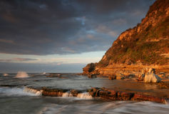Rocky shore line at sunrise Stock Images