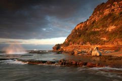 Rocky shore line at sunrise. Beautiful saturated colours of early morning at a rocky shoreline with water flowing in slow motion. Storm clouds gathering in the stock images