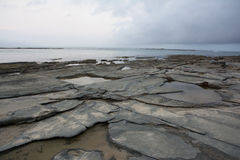 Rocky shore line at sunset. Flat rock formation on the oceans edge with water at sunset Stock Image