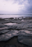 Rocky shore line at sunset. Flat rock formation on the oceans edge with water at sunset Stock Photography