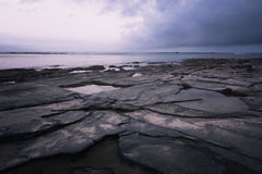 Rocky shore line at sunset. Flat rock formation on the oceans edge with water at sunset Stock Images