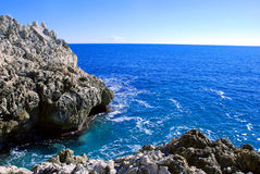 Rocky shore of the Mediterranean Sea on a clear day. In the blue sea water is splashing at the foot of the rocky shore Royalty Free Stock Images