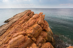 Rocky shore by minerals of the red color, the Aegean sea Royalty Free Stock Photography