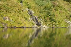 Rocky shore of a mountain lake. A picturesque rocky shore of a calm mountain lake with a waterfall on a bright sunny day Stock Photography