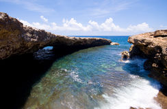 Rocky shore with natural bridge. Rocky shore with ocean waves with natural brige Stock Photo