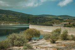 Rocky shore next to the concrete dam of Rossim Lake. Rocky shore with bushes next to the concrete dam of Rossim Lake, in a sunny day at the highlands of Serra da royalty free stock photography