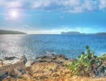 Rocky shore in Porto Conte with Capo Caccia on the background Stock Image