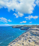Rocky shore in Porto Torres under huge clouds Royalty Free Stock Image
