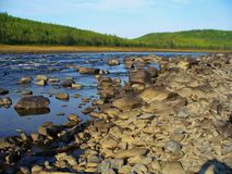Rocky shore of river Stock Images