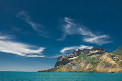 Rocky shore sea cliffs. And blue sky with clouds Royalty Free Stock Image