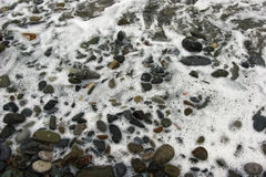 Rocky shore with sea foam Stock Photography