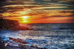 Rocky shore under a colorful sky in Sardinia Stock Photos