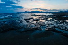 Rocky shore washed by sea waves in evening. Marine landscape royalty free stock photos