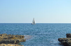 A Rocky Shore And A Yacht Royalty Free Stock Image