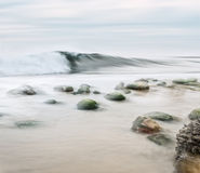 Rocky Shorebreak. A high key seascape with desaturated colors.  Image made with panning motion for a semi-blurred effect Stock Photography
