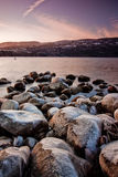 Rocky shoreline. An image at sunset in the winter, with frozen rocks on the shore Stock Photo