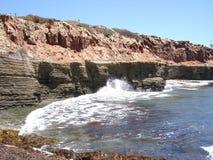 Rocky Shoreline. Rocky Ocean Shoreline with Layered Erosion and Crashing Waves Stock Images