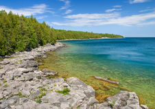 Rocky shoreline of beautiful Georgian Bay. Rocky coastline of Lake Huron with blue sky reflecting in the water Stock Image