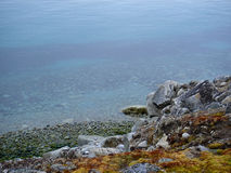Rocky shoreline calm water. Rocky, barren shore or coastline and calm water royalty free stock photo