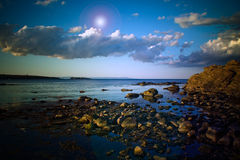 Rocky shoreline and clouds 1 Stock Images