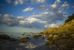 Rocky shoreline and clouds. A view along a rocky shoreline or coast with large, white and silver clouds in a blue sky royalty free stock images