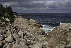 Rocky shoreline with cloudy skies. And waves seen between the rocks Stock Photos
